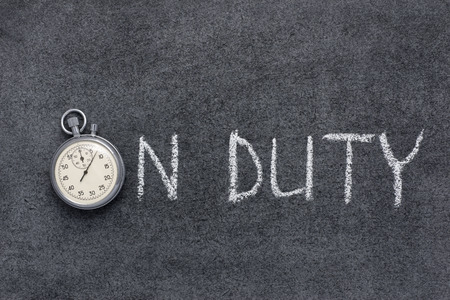 on duty phrase handwritten on chalkboard with vintage precise stopwatch used instead of O Фото со стока