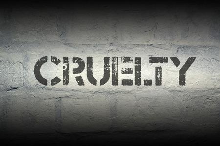 cruelty: cruelty stencil print on the grunge white brick wall