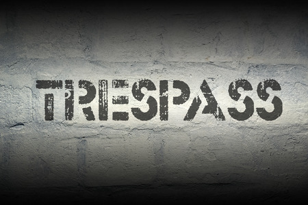 trespass: trespass stencil print on the grunge white brick wall Stock Photo