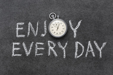 every: enjoy every day phrase handwritten on chalkboard with vintage precise stopwatch used instead of O Stock Photo
