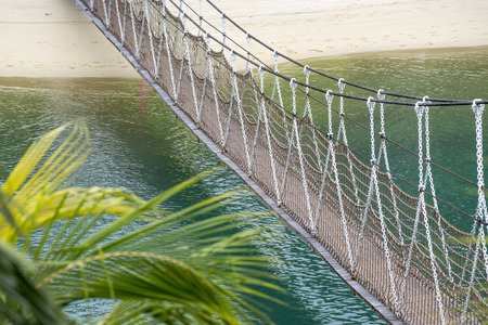 hanged: scenic hanged pedestrian rope bridge over blue sea water Stock Photo