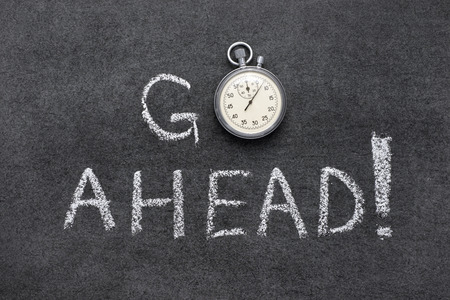 go ahead: go ahead exclamation handwritten on chalkboard with vintage precise stopwatch used instead of O