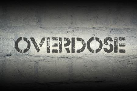 overdose: overdose stencil print on the grunge white brick wall