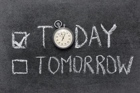precise: today or tomorrow concept handwritten on chalkboard with vintage precise stopwatch used instead of O Stock Photo