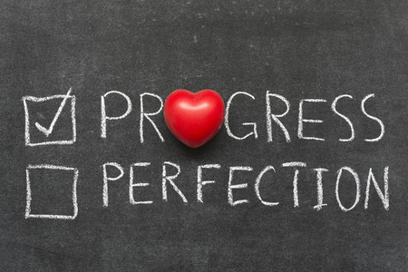 choose progress not perfection concept handwritten on blackboard with heart symbol instead of O Stockfoto