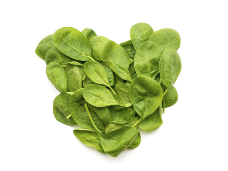 arranged: fresh green spinach leaves arranged in shape of heart Stock Photo