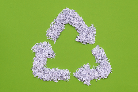 recycle symbol made from heap of shredded white paper over green