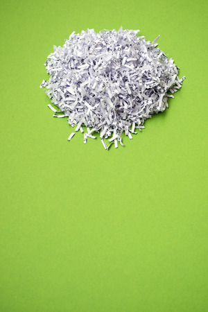 shredded paper: shredded paper heap on the bright green background Stock Photo