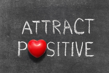attract: attract positive phrase handwritten on blackboard with heart symbol instead of O Stock Photo