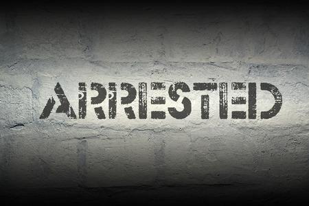 detained: impresi�n de la plantilla arrestado en la pared de ladrillo blanco de grunge Foto de archivo