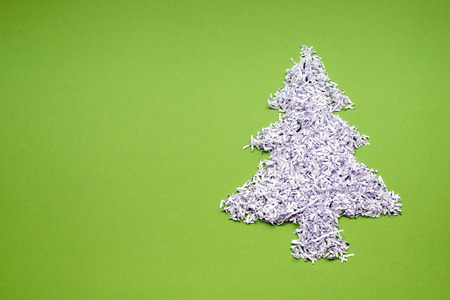 ecology recycle concept with fir tree symbol made from shredded white paper over green