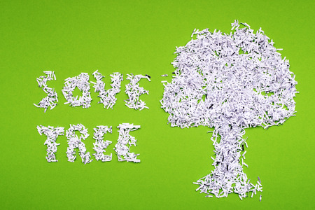 shredded paper: save tree concept made from shredded paper on green background