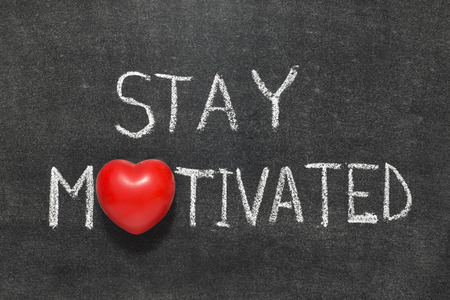 stay motivated phrase handwritten on blackboard with heart symbol instead of O