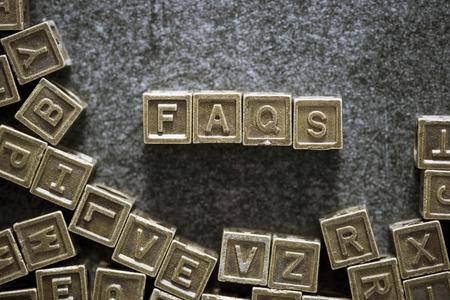 faq's: FAQs word made from metallic blocks on blackboard surface