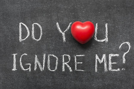 ignore: do you ignore me question handwritten on blackboard with heart symbol instead of O Stock Photo