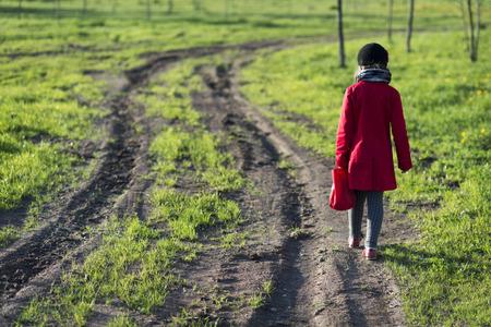 lejos: chica de la capa roja que va muy lejos por el camino rural sucio, el enfoque selectivo en chica
