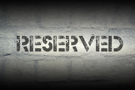 booked: reserved stencil print on the grunge white brick wall