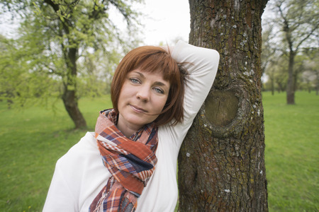 checkered scarf: head shot  portrait of woman in white sweater and fashion scarf near the tree in springtime park