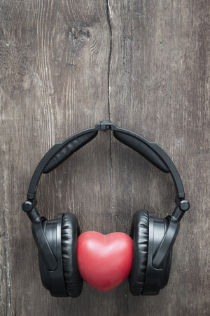 black headphones with red heart on rustic wooden background