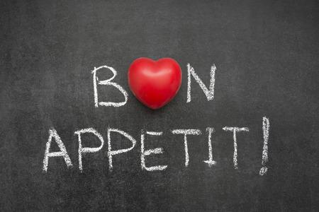 bon appetit exclamation handwritten on blackboard with heart symbol instead of O Banco de Imagens