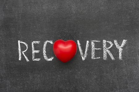decease: recovery word handwritten on blackboard with heart symbol instead of O Stock Photo