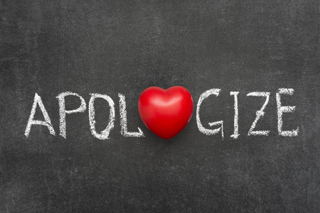 apologize: apologize word handwritten on blackboard with heart symbol instead of O Stock Photo