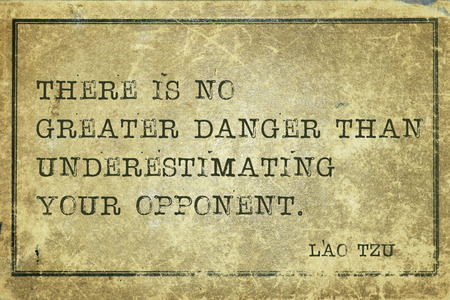 underestimate: There is no greater danger than underestimating - ancient Chinese philosopher Lao Tzu quote printed on grunge vintage cardboard Stock Photo