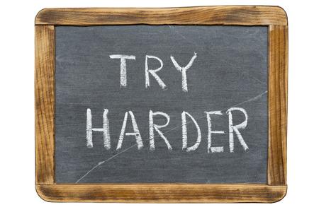 harder: try harder slogan handwritten on vintage slate chalkboard isolated on white Stock Photo