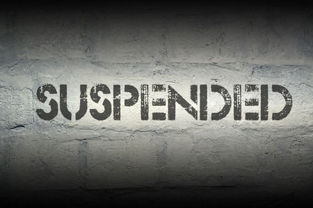 interruption: suspended stencil print on the grunge white brick wall