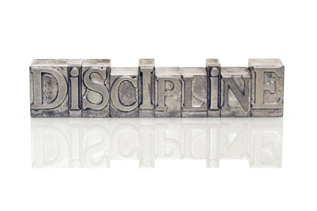 discipline word made from metallic letterpress type on reflective surface Фото со стока