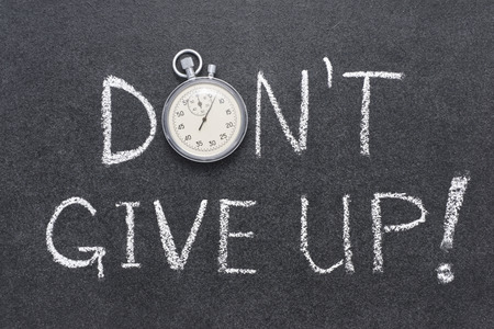give up: don't give up exclamation handwritten on chalkboard with vintage precise stopwatch used instead of O
