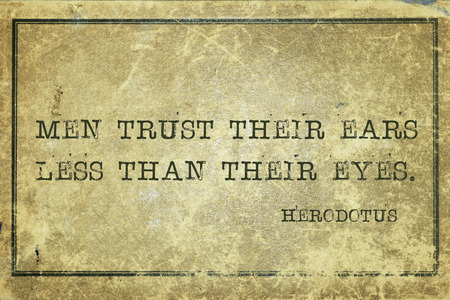 historian: Men trust their ears less than their eyes - ancient Greek historian Herodotus quote printed on grunge vintage cardboard Stock Photo