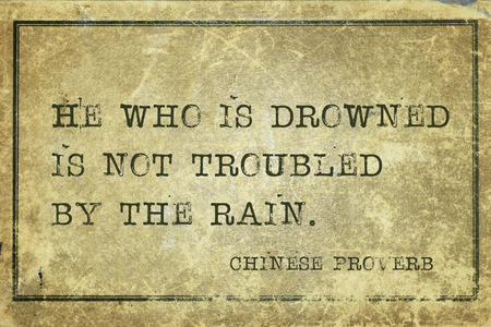 proverb: He who is drowned is not troubled by the rain - ancient Chinese proverb printed on grunge vintage cardboard Stock Photo