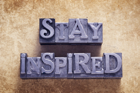 inspired: stay inspired message made from metallic letterpress type on vintage cardboard