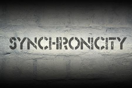 synchronicity stencil print on the grunge white brick wall