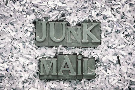 junk mail: junk mail phrase made from metallic letterpress type inside of shredded paper heap