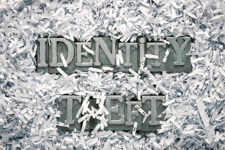 identity theft: identity theft phrase made from metallic letterpress type inside of shredded paper heap Stock Photo