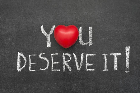 deserve: you deserve it exclamation handwritten on chalkboard with heart symbol instead of O
