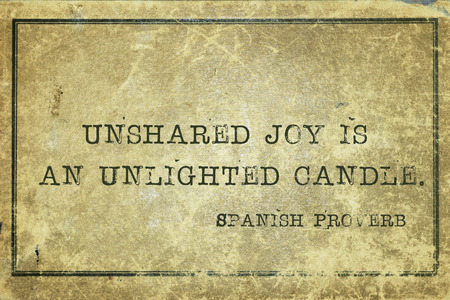 proverb: Unshared joy is an unlighted candle - ancient Spanish proverb printed on grunge vintage cardboard