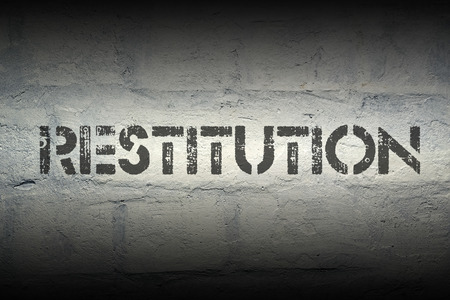 restitution: restitution stencil print on the grunge white brick wall Stock Photo