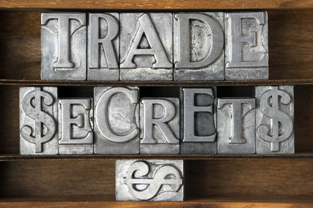 trade secret: trade secrets phrase with dollar sign made from metallic letterpress type on wooden tray Stock Photo