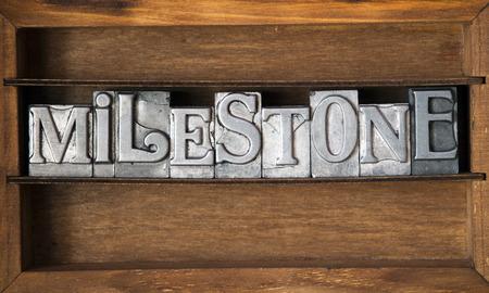 milepost: milestone word made from metallic letterpress type on wooden tray