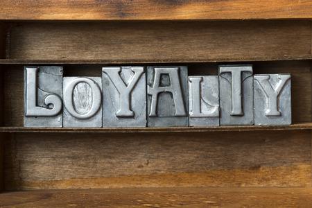 letterpress type: loyalty word made from metallic letterpress type on wooden tray Stock Photo