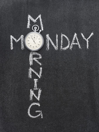 Monday morning phrase handwritten on chalkboard with vintage precise stopwatch used instead of O