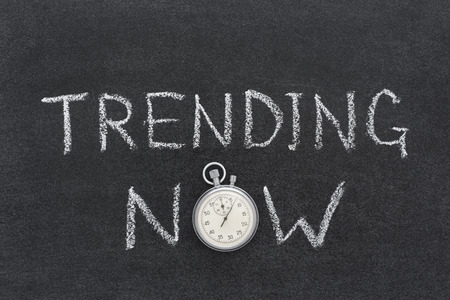 trending: trending now phrase handwritten on chalkboard with vintage precise stopwatch used instead of O