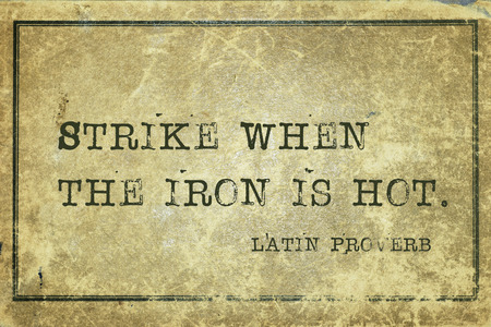 ancient philosophy: Strike when the iron is hot - ancient Latin proverb printed on grunge vintage cardboard Stock Photo