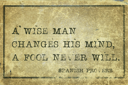 proverb: A wise man changes his mind - ancient Spanish proverb printed on grunge vintage cardboard