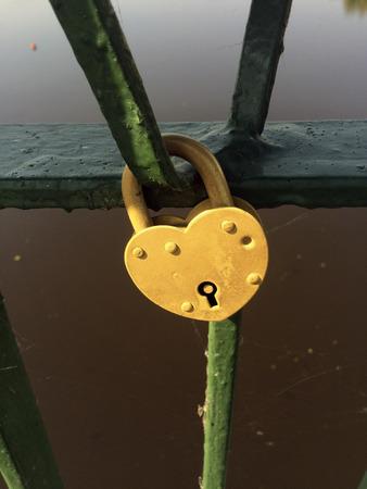 hanged: yellow padlock hanged on the bridge fence