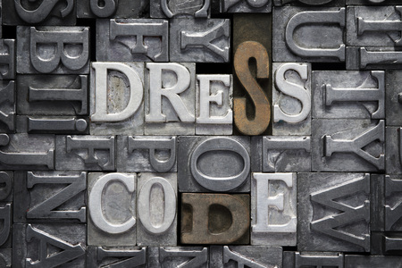 to dress: dress code phrase made from metallic letterpress type with letter blocks background