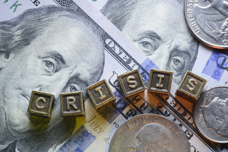 money issues: crisis word made from metallic letter blocks over dollar banknotes Stock Photo